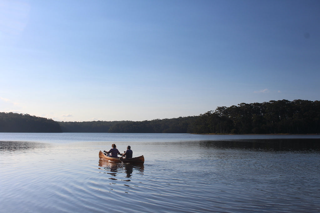 Keith and Nicki Endt paddle a Champlain wooden canoe across a calm lake