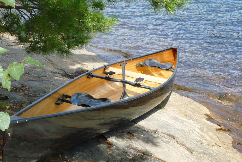 A composite canoe sits on a rock shelf beside the water