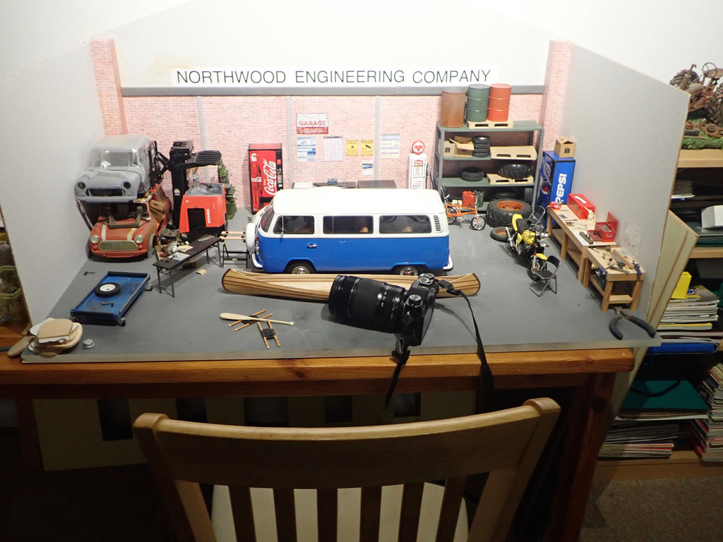 A scale model VW bus and wooden canoe sit on a desk with a camera positioned nearby