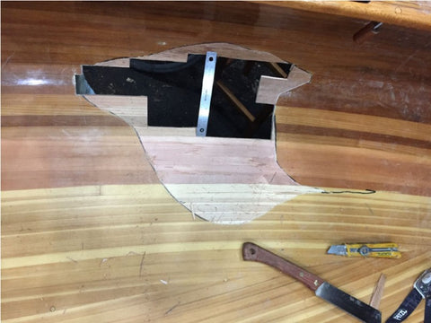Hole in canoe hull with ruler for scale