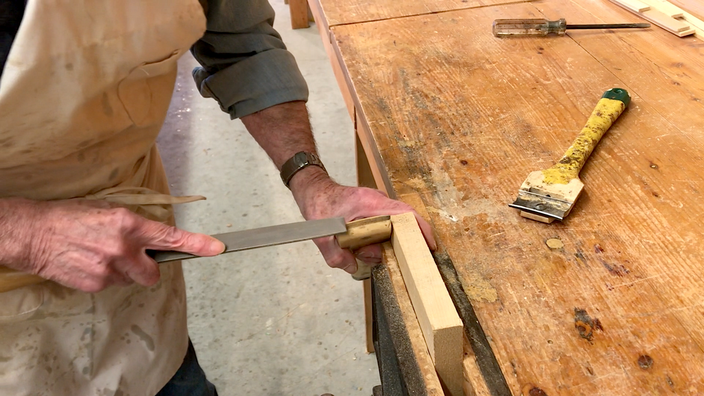 Ted Moores files the blade of a Richard paint scraper to a custom curvature, with the scraper braced against a work table and a second scraper seen beside it