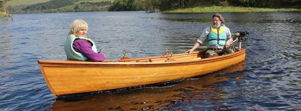 Jon Belton sits in the stern of skiff with a woman in the bow