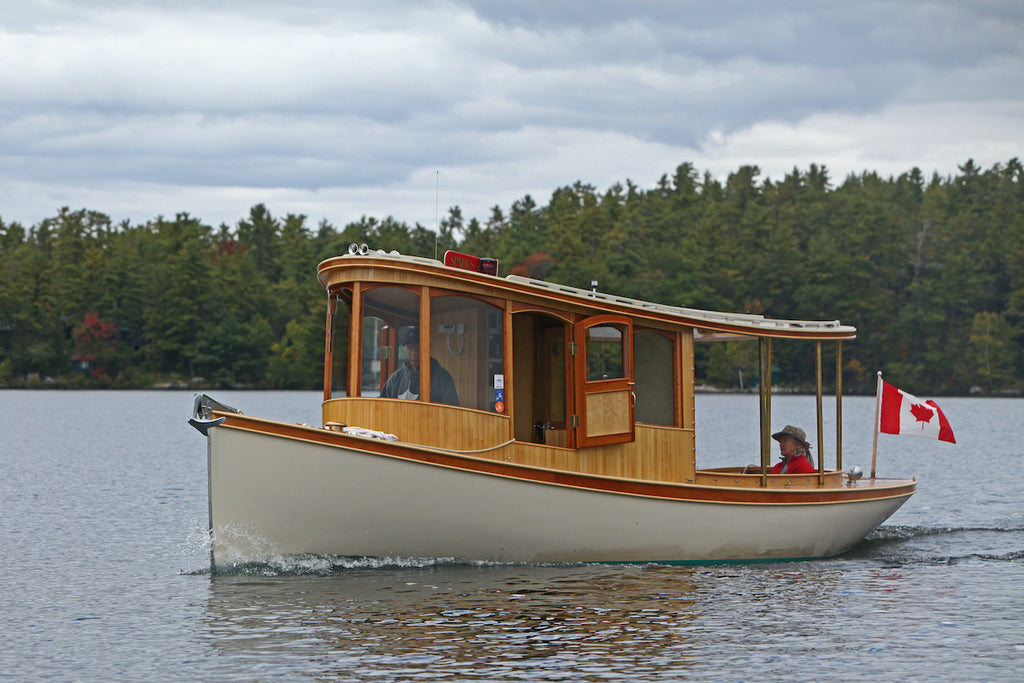 An electric fantail launch cruises along a lake