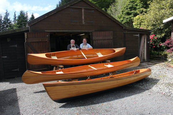 Jon Belton and his friend stand side by side in front of the three wooden boats they built together