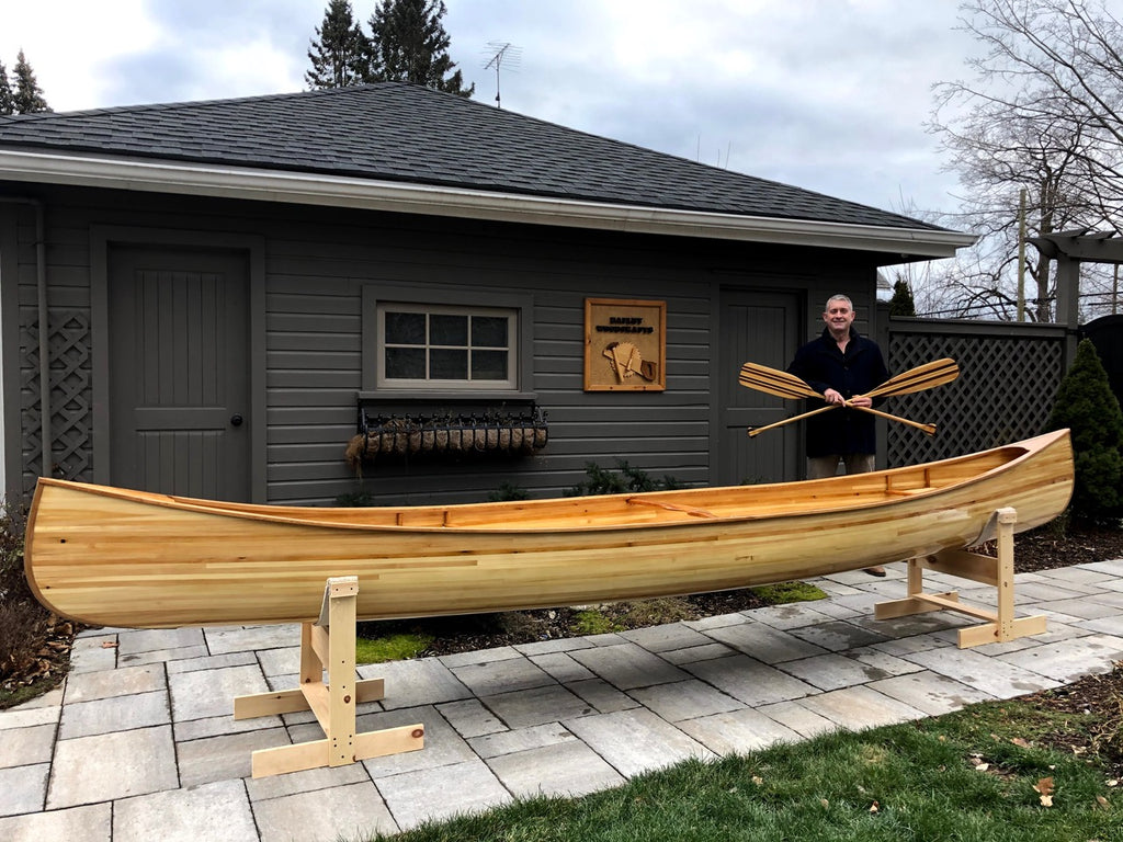 Ty Bailey stands behind his newly completed Nomad 17 holding a pair of crossed paddles