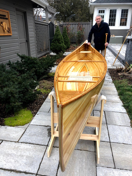 Photo looking down the bow of a Nomad 17 canoe while the builder stands at the stern