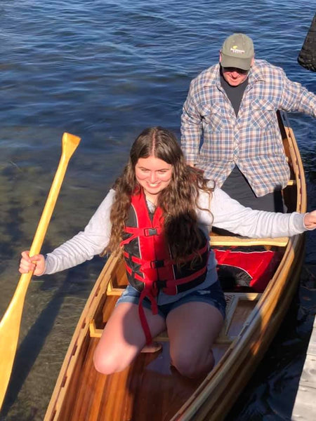 William John Beyette and granddaughter Zara get into their newly built Bob's Special canoe beside a dock