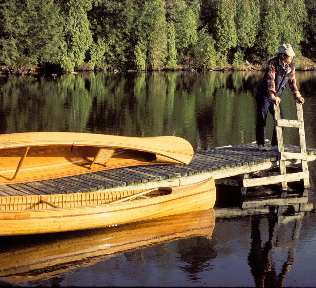 Ted Moores leans on the ladder of a dock, with two examples of woodstrip canoes beside him (recognizable as similar to the cover of Canoecraft to fans of the book)