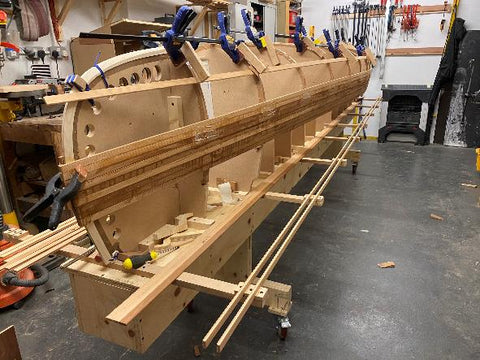 Canoebuilding molds and strongback with a handful of planks already installed