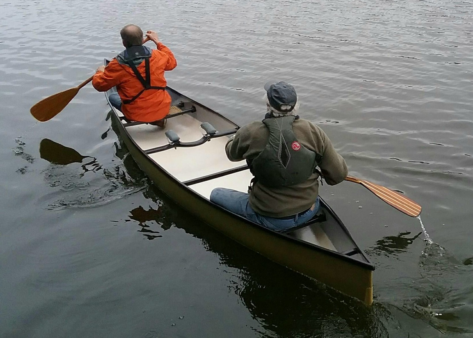 Randy Pfeifer and a paddling partner, seen from behind, test his composite canoe on the water