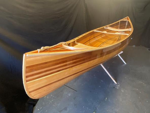 A Ranger 15 wooden canoe, positioned in front of a black backdrop