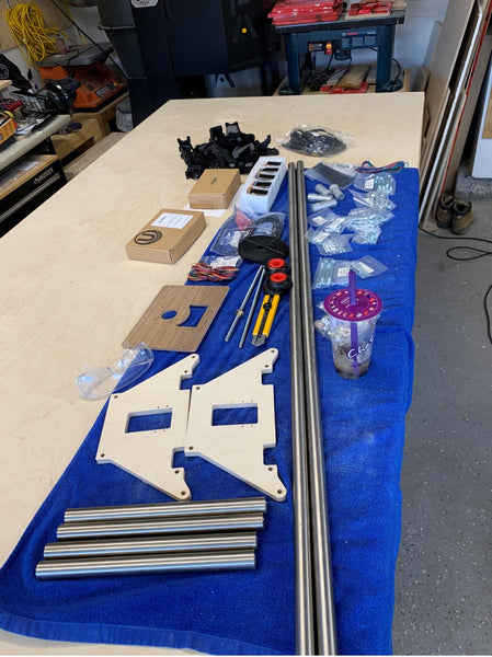 Parts for a mostly printed CNC machine laid out on a blue towel