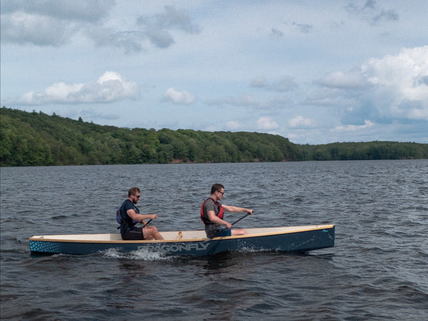 Two paddlers test a prototype of a dragonboat-style trainer boat on Upper Rideau Lake