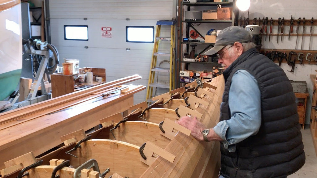 Ted Moores works on planking the hull of an unfinished C4 racing canoe