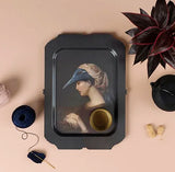 Dark melamine serving tray with surreal image of woman with bird on head.