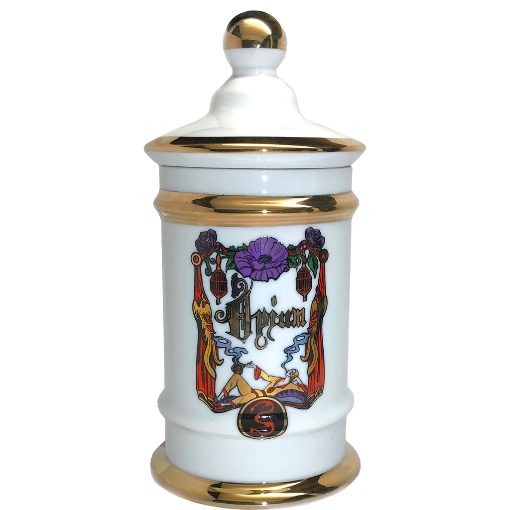 Large apothecary vessel with gold detail and print on front. Vessel contains candle