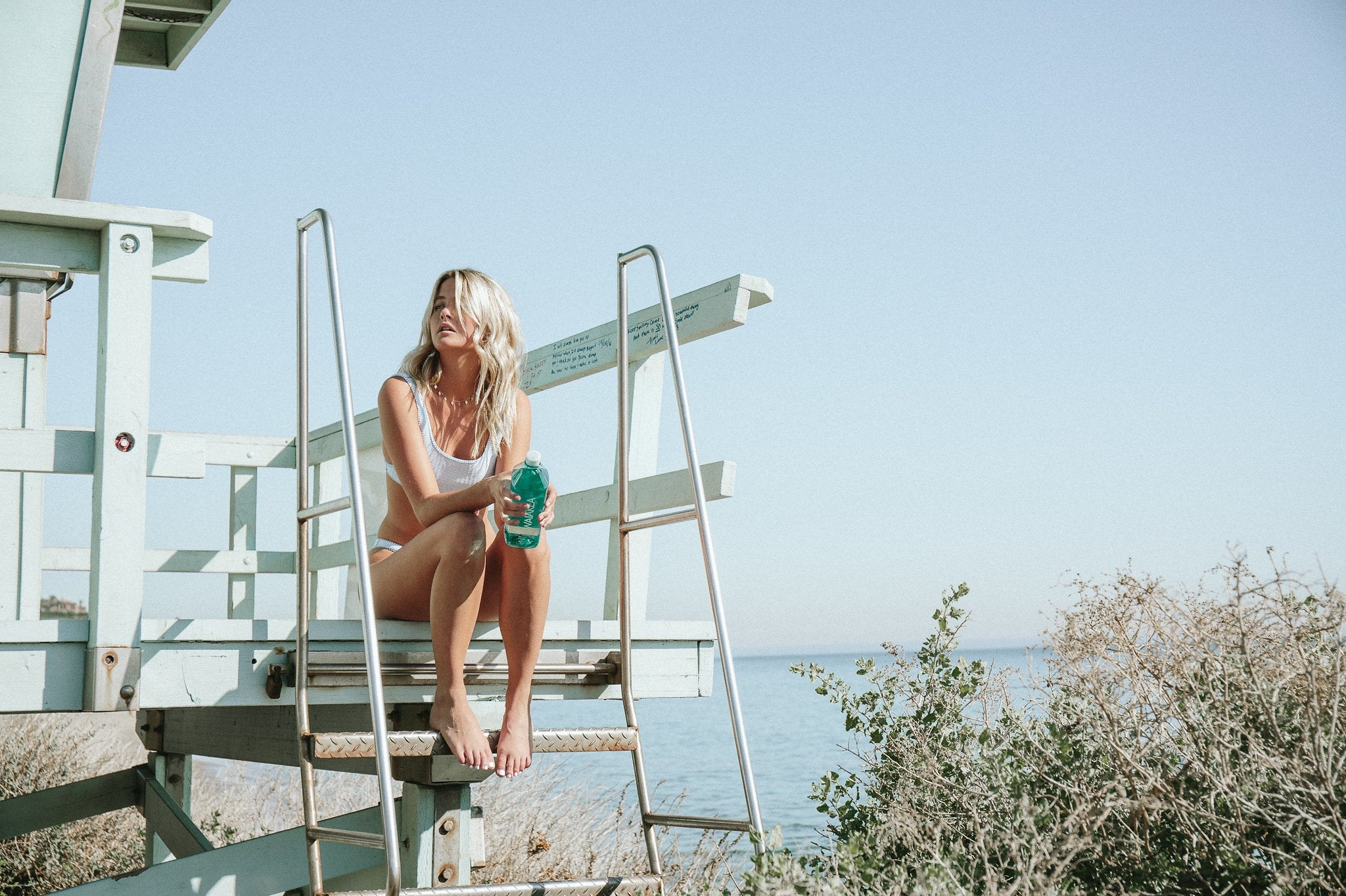 A woman in a bathing suit sitting on a lifeguard tower