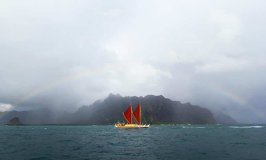 Hōkūle'a passing in front of a mountain with a rainbow overhead