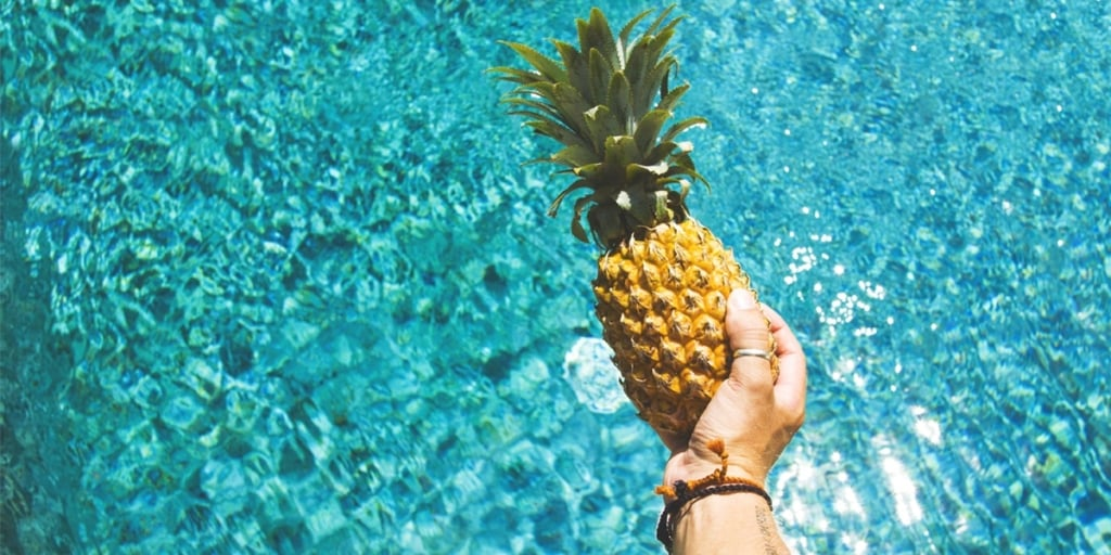 Person holding a pineapple above a pool