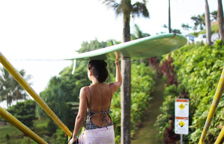 Woman walking with a surfboard on her head