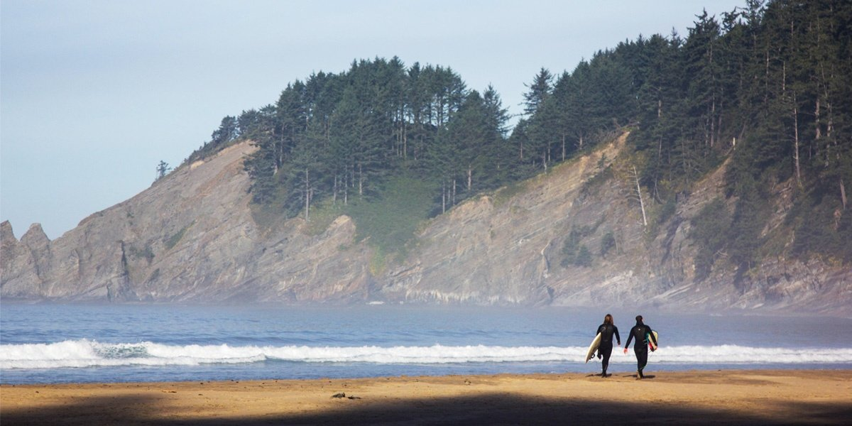 Two people heading into the surf on the Oregon coast