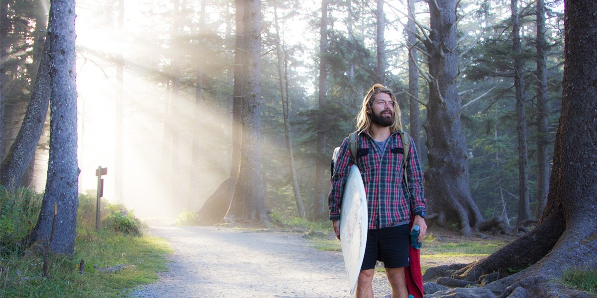 Man with a surfboard surrounded by forest