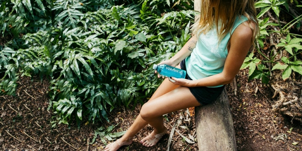 Woman sitting on a log in a rainforest, holding a bottle of Waiakea water