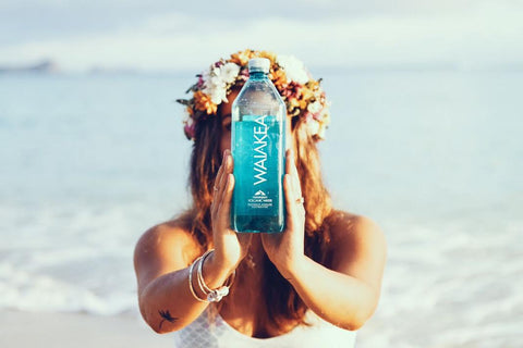 Woman holding up a bottle of Waiakea water on the beach