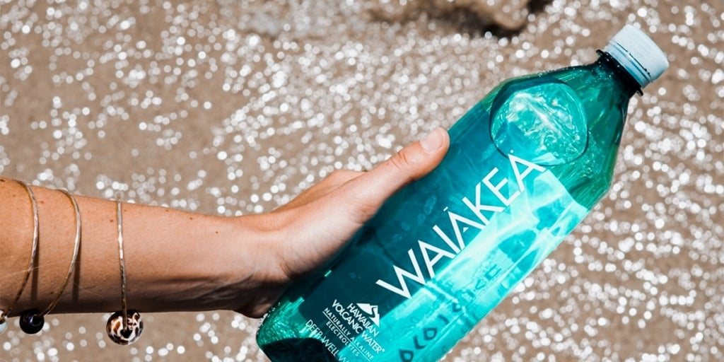 Person holding a bottle of Waiakea water over the incoming tide