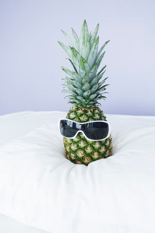 A pineapple wearing sunglasses on a pillow