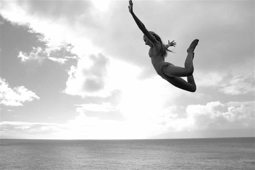 Monochromatic image of woman belly-flopping into the ocean