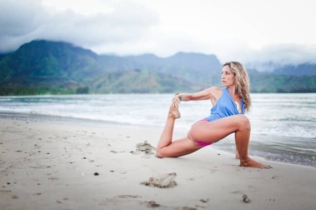 Woman stretching her leg on the beach