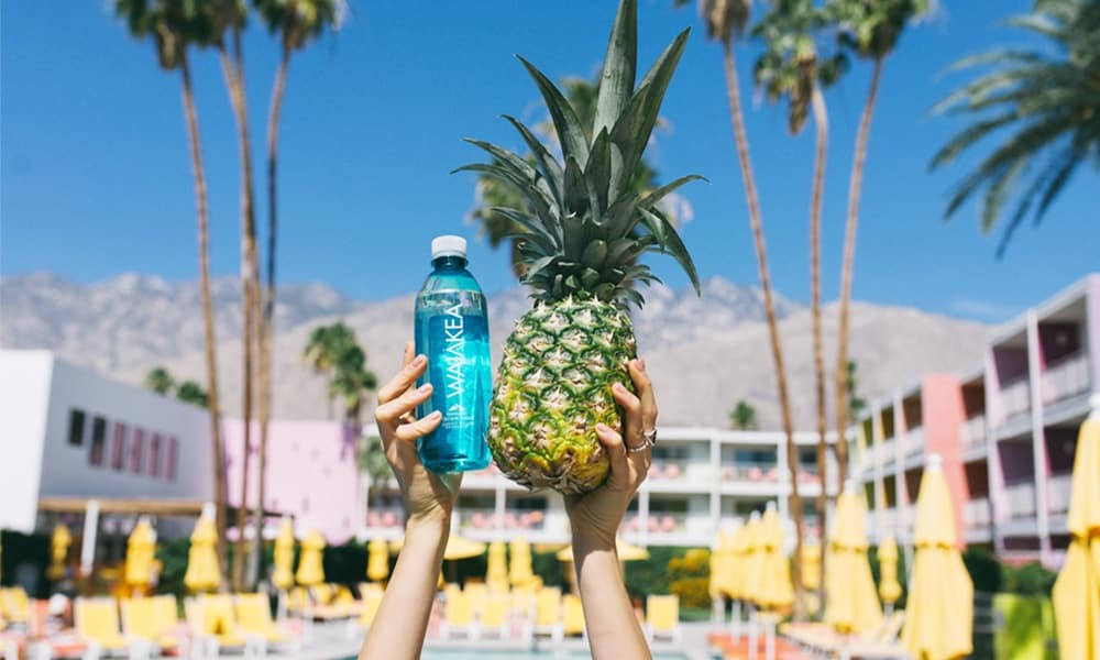 Person holding up a pineapple and Waiakea bottle