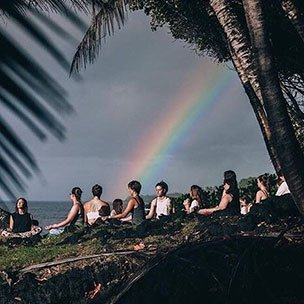 Group meditating outside under a rainbow
