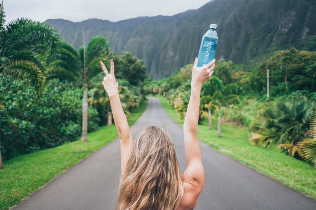 Person holding a bottle of Waiakea water making peace sign