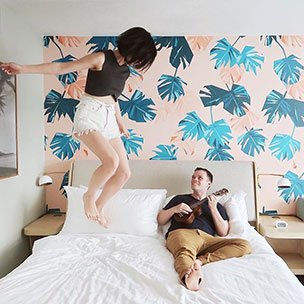 Woman jumping on bed while a man plays a ukulele