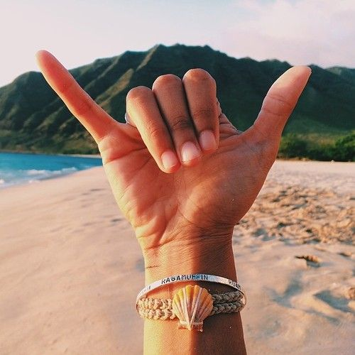 Hand throwing a shaka on the beach in front of a mountain