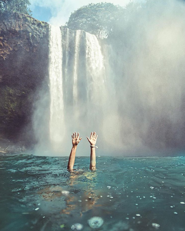 Hands reaching out from under water in front of a waterfall