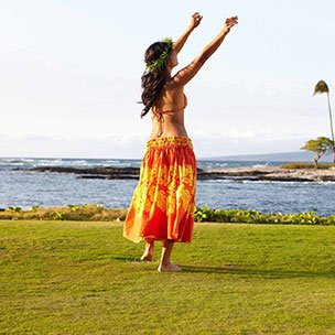 Woman wearing grass skirt, dancing by the sea