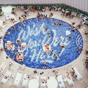 """Pool from overhead with tiling that reads """"Wish You Were Here!"""