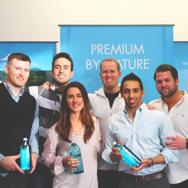 The Waiakea team each holding a bottle of Waiakea