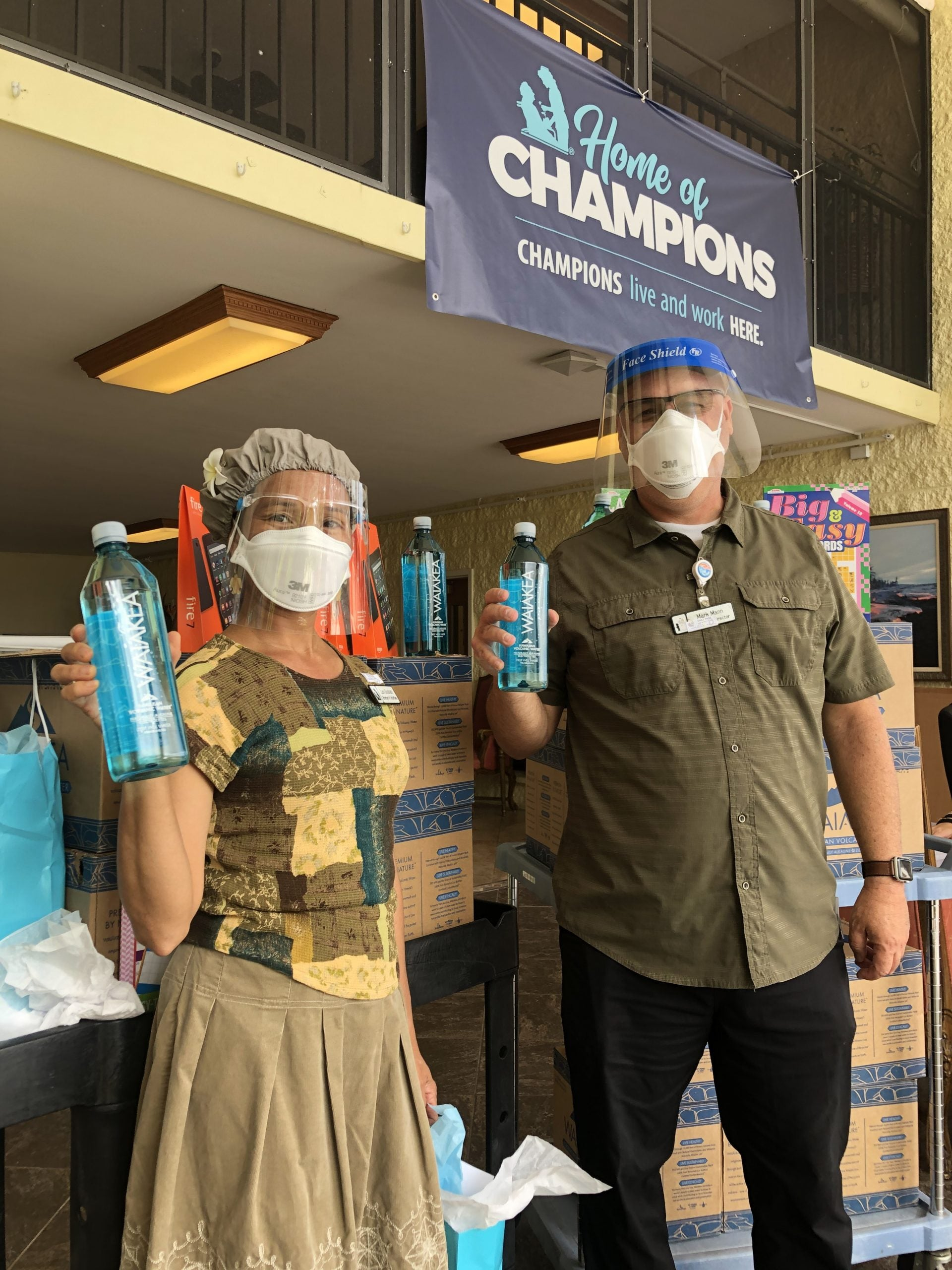 Man and woman each holding a bottle of Waiakea water