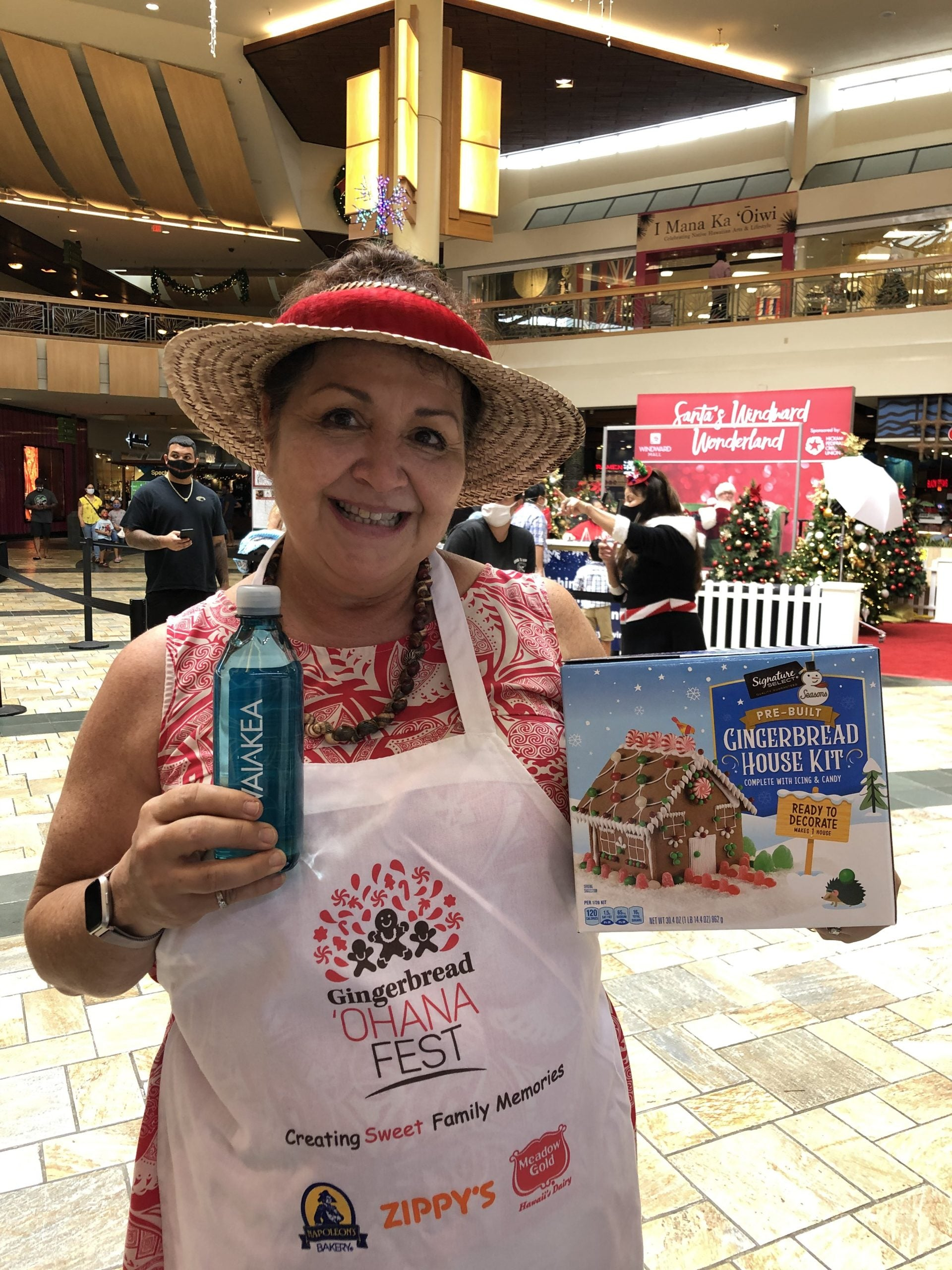 Woman holding Waiakea water and gingerbread house kit