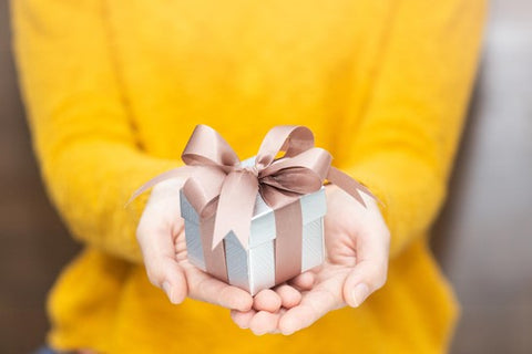 a woman in a yellow jumper holding out a meaningful gift with a ribbon around it.
