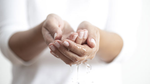 a person washing their hands at a sink