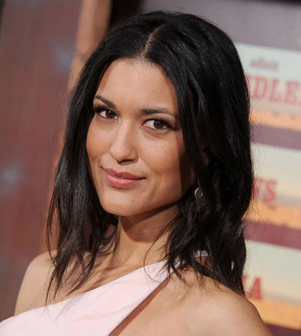 Julia Jones, smiling slightly and looking at the camear