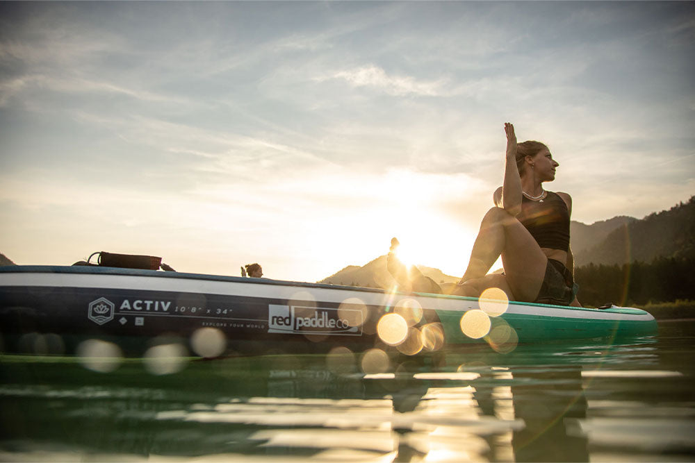 Women Sat On Red Paddle Co Activ 108 Paddle Boards Doing Yoga