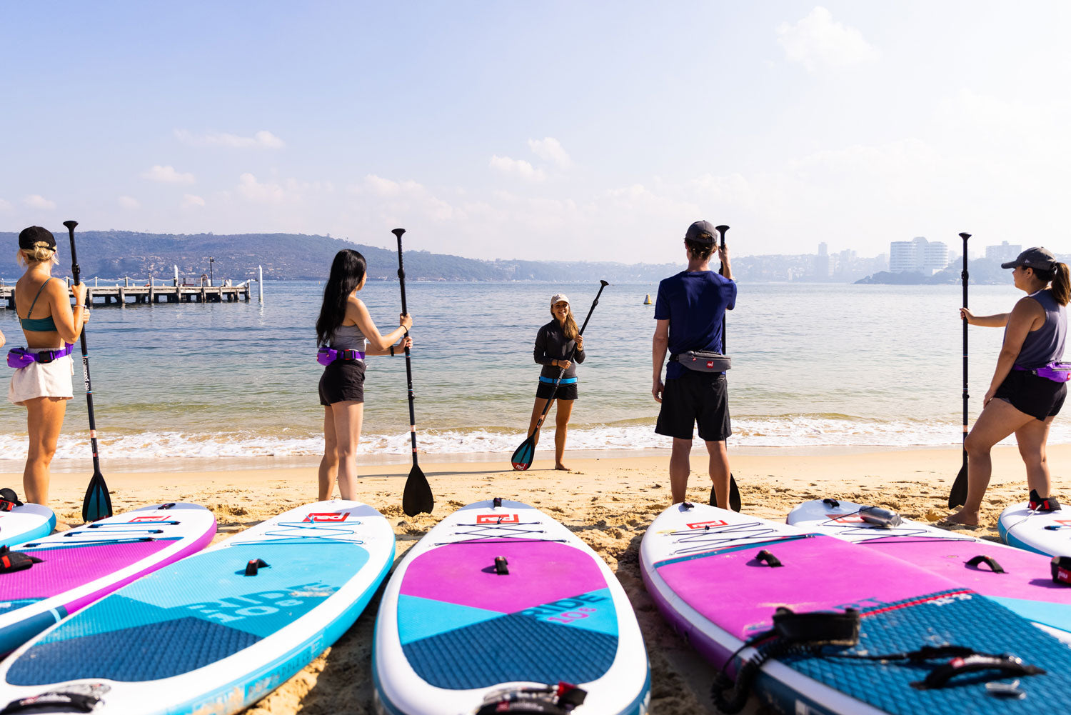 Paddlers listen to instructor on beach