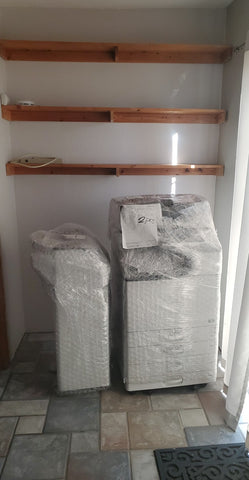 Image of a big white printer wrapped in plastic
