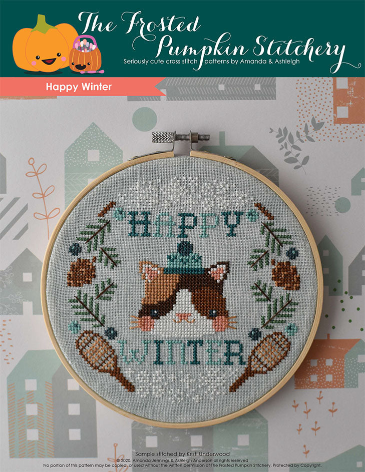 "Happy Winter counted cross stitch pattern. This pattern features a cat wearing a winter cap surrounded by the words ""Happy Winter,"" pine boughs, pine cones, snowshoes, snowflakes and juniper berries."